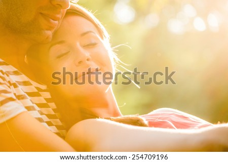 Intimate moments - young couple embracing and hugging in nature - stock photo