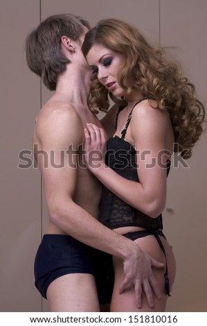 intimate young adult couple during foreplay in bed - stock photo