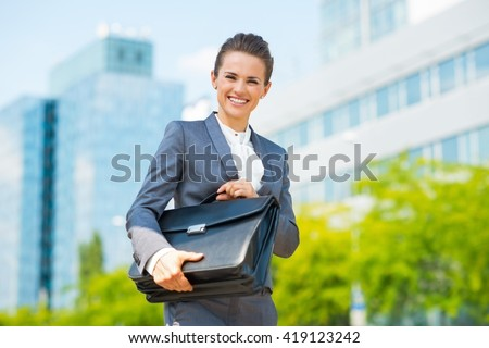 Into the ultra-modern business trends. Portrait of smiling business woman in modern office district holding briefcase - stock photo