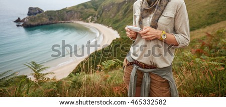 Into the wild in Spain. happy adventure woman hiker writing sms in front of ocean view landscape