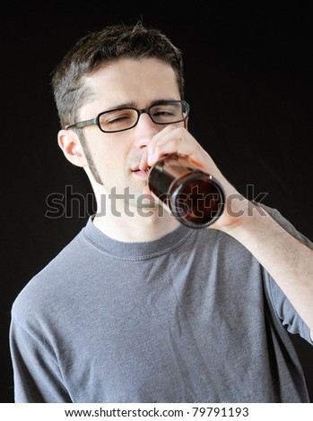Intoxicated young man drinking out of a brown beer bottle. - stock photo