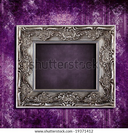 Intricate old frame hanging on grungy violet vintage wallpaper - stock photo
