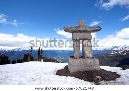 Inukshuk at the top of Whistler Peak in British Columbia, Canada, with snow, blue sky, white clouds and mountains in the distance - stock photo