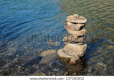 Inukshuk in the clear waters of Moraine Lake with ripples - stock photo