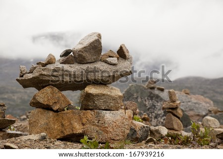 inukshuk in yukon by misty mountains - stock photo