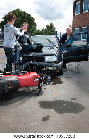 Inured woman getting out of her car to see the how the motorist she has crashed into is doing - stock photo