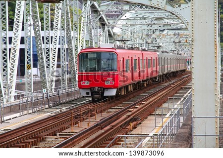 Inuyama, Japan - town in Aichi prefeture of the region Chubu. Red train crosses railway bridge over Kiso river.