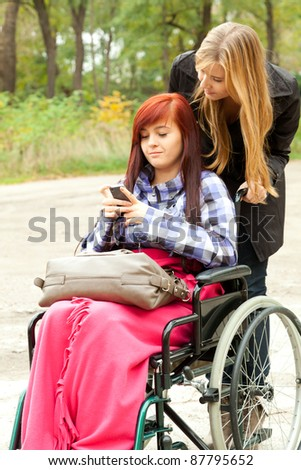 invalid girl on the wheelchair with mobie phone and friend outdoors
