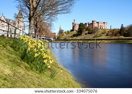 Inverness, Highlands, Scotland with spring daffodils and the River Ness in the foreground and the castle in the background.
