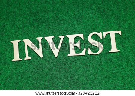 Invest word on rusty green background. Business concept