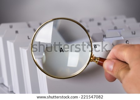 Investigating documents with magnifying glass over black background - stock photo