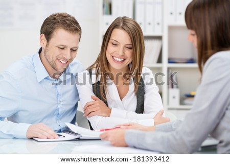 Investment adviser giving a presentation to a friendly smiling young couple seated at her desk in the office - stock photo