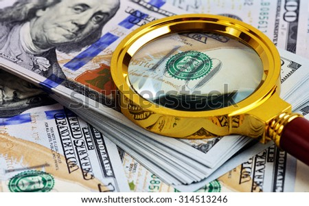 Investment analysis. Stack of US Dollar and magnifying glass - stock photo
