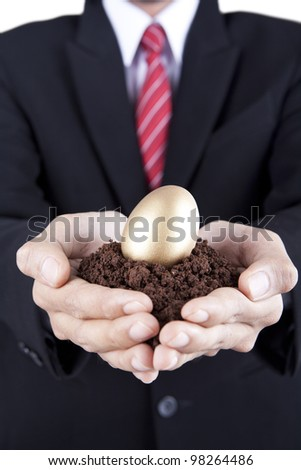 Investment concept businessman showing a golden egg and soil - stock photo