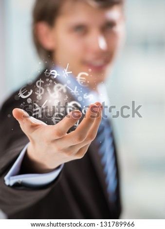 Investment concept. Handsome business man with currency symbols. - stock photo