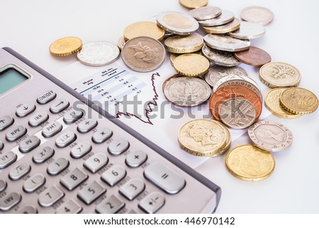 Investment concept. International money coins and financial calculator place on stock graph.
