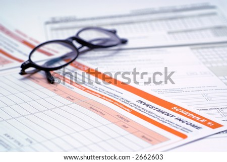 Investment tax form with glasses - selective focus on the word investment - stock photo
