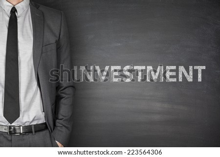 Investment word on black blackboard with businessman - stock photo