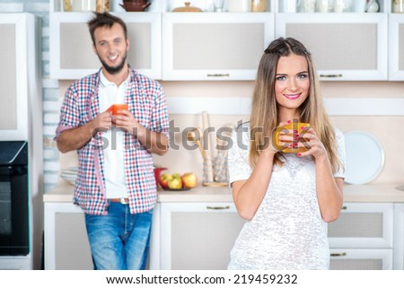 Invigorating drink. Young loving girl drinking hot tea while her boyfriend stands in the kitchen and holding a cup looking and smiling at the camera - stock photo