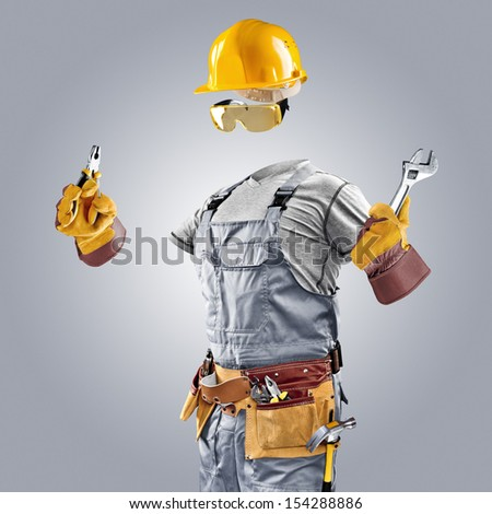 invisible builder with wrench and pliers on grey background - stock photo