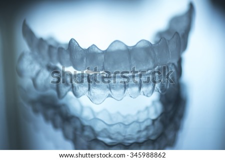 Invisible dental teeth brackets tooth aligners plastic braces retainers to straighten teeth. Orthodontic temporary removable straighteners in dental office dentists surgery  - stock photo