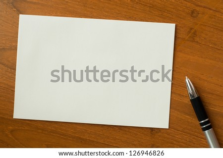 invitation card with pen on wood table - stock photo