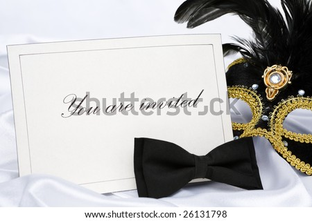 Invitation to mask party place on white satin - stock photo