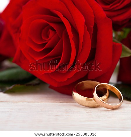 Invitation Wedding rings and red roses on wooden desk, square. Selective focus, the background is blurred - stock photo