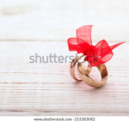 Invitation wedding rings with red ribbon on white wooden desk, square Selective focus, background is blurred - stock photo