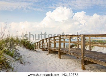Inviting boardwalk through the sand dunes on a beautiful beach in the early morning. Beautiful puffy clouds in the sky. - stock photo