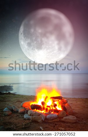 Inviting campfire on the beach during the summer. moon over the sea. instagram style. vintage retro. tilt-shift blur - stock photo