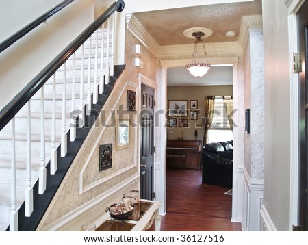 Inviting entranceway in an expensive modern American home. A sofa, piano and window in the living room are visible in the background. - stock photo
