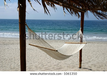 Inviting hammock on the beach - stock photo