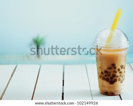 Inviting iced drink in a covered cup on a warm day at the seashore. - stock photo
