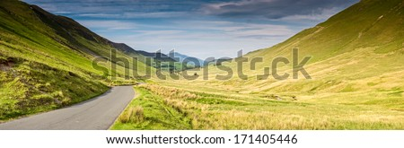 Inviting road heading to a picturesque horizon, Lake District, UK. - stock photo