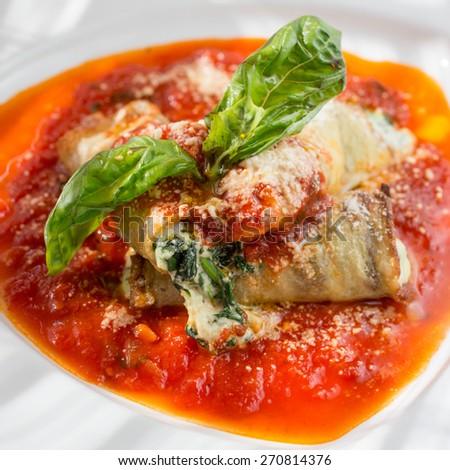 Involtini di Melanzane. Stuffed eggplant, three cheese, baby spinach,  speck and pomodoro sauce  - stock photo