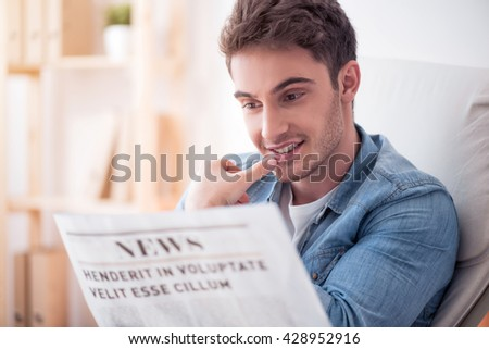 Involved in news. Cheerful delighted handsome man reading newspeper and smiling while resting
