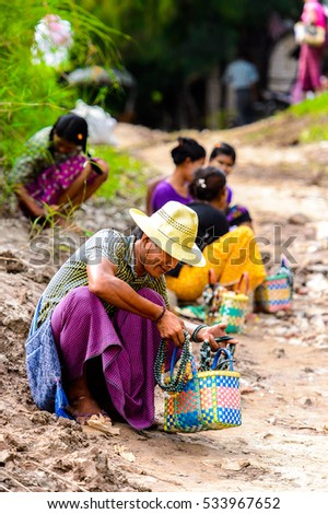 INWA, MYANMAR - AUG 25, 2016: Unidentified Burmese man offers souvenirs for sale. 68 per cent of  Myanma people belong to Bamar ethnic group
