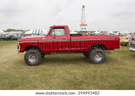 IOLA, WI - JULY 12:  Side of 1977 Red Ford F150 Pickup Truck at Iola 42nd Annual Car Show July 12, 2014 in Iola, Wisconsin. - stock photo