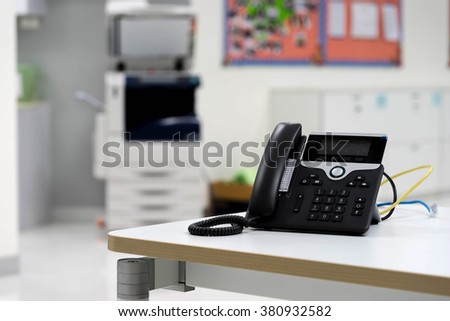 IP phone on desk in office and paper copier machine