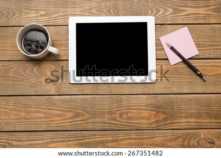 Ipad. Digital tablet computer with sticky note paper and cup of coffee on old wooden desk. Simple workspace or coffee break with web surfing. - stock photo