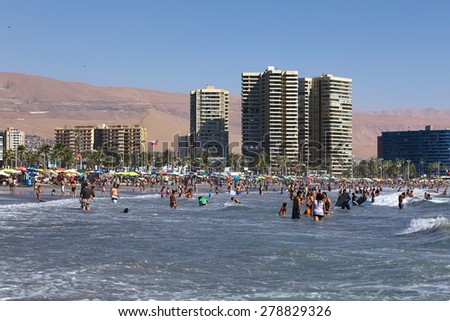IQUIQUE, CHILE - FEBRUARY 10, 2015: Unidentified people bathing in the Pacific ocean at Cavancha beach on February 10, 2015 in Iquique, Chile. Iquique is a popular beach town in Northern Chile.
