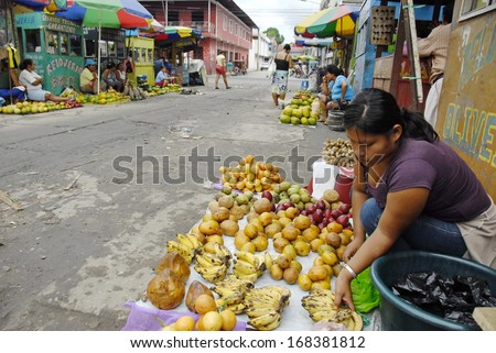IQUITOS, PERU - APRIL 30: Unidentified Peruvian woman sells exotic fruits on a street of Iquitos, Peru on April 30, 2010. Amazon Peru is known for the rich variety of exotic fruits unknown beyond.  - stock photo