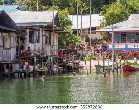 Iquitos, Peru- May 16, 2016: Wooden houses on stilts on water in a small village on the Lake Sentani