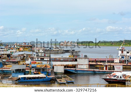 IQUITOS, PERU - OCTOBER 11, 2015: Boats at dock in the Itaya River. Iquitos is the largest metropolis in the Peruvian Amazon, and the sixth most populous city of Peru. - stock photo