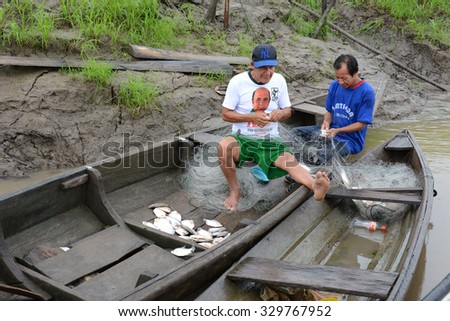 IQUITOS, PERU - OCTOBER 16, 2015: Peruvian fishermen and their catch. Fish are an important food source for the people of the Peruvian Amazon. - stock photo