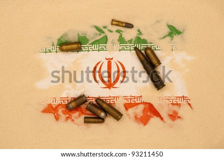 Iran flag covered in sand with different ammunition scatter on it - stock photo