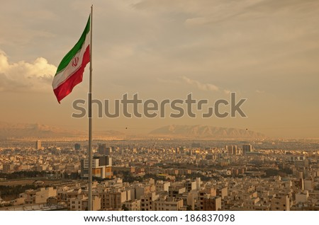 Iran flag waving  in the wind above skyline of Tehran lit by orange glow of sunset.