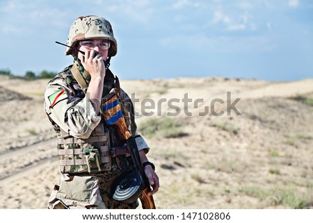 iraqi soldier in the desert talking portable radio station - stock photo
