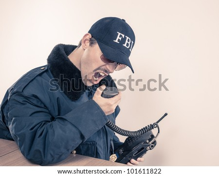 Irate Federal officer in blue coat yelling for something on vintage radio during a crises at table - stock photo